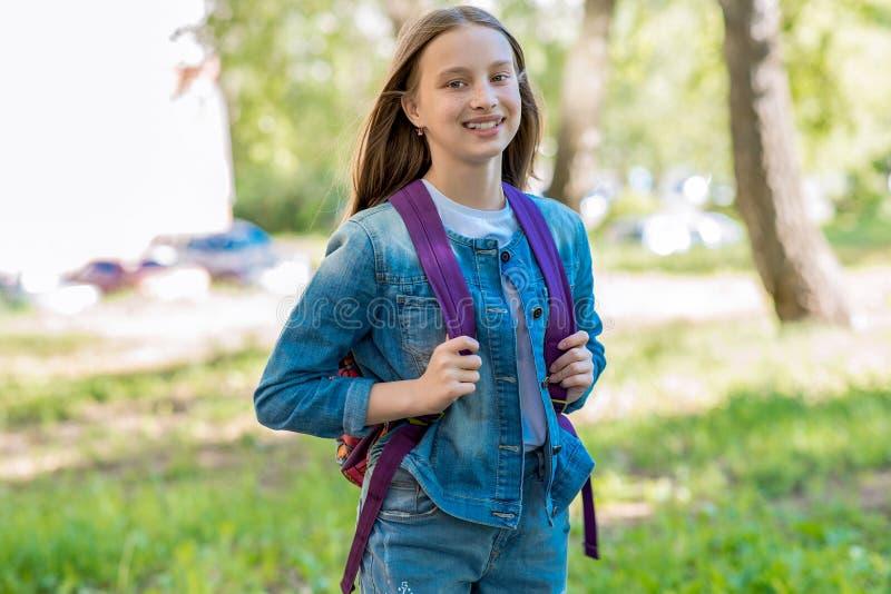 Una ragazza della scolara sta sorridendo di estate in parco Dietro lo zaino Concetto di nuovo alla scuola Emozioni di felicità e fotografia stock libera da diritti