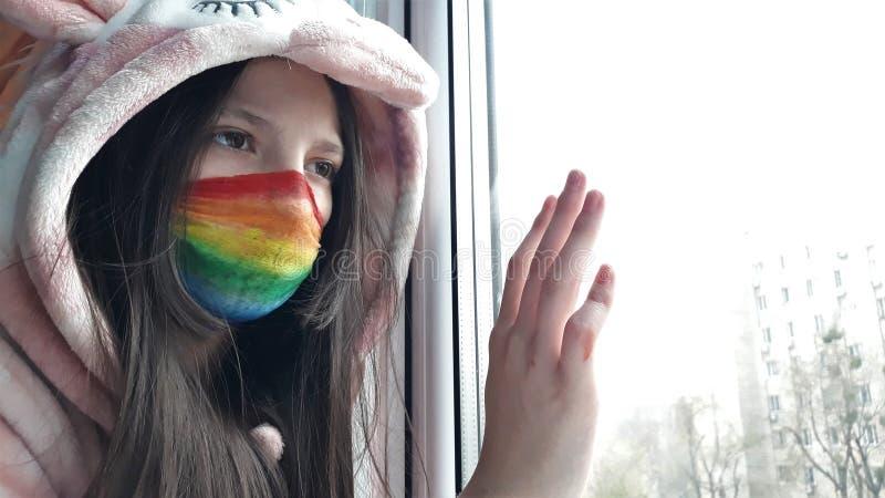 Una ragazza di Brunette con una maschera medica dipinta in colori brillanti d'arcobaleno è in piedi davanti alla finestra con la  fotografia stock