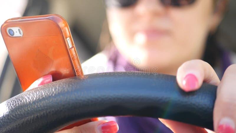 Una ragazza di buon umore alla ruota di un'automobile, aderisce alla ruota, batte su con le sue dita, balli, immagine stock libera da diritti
