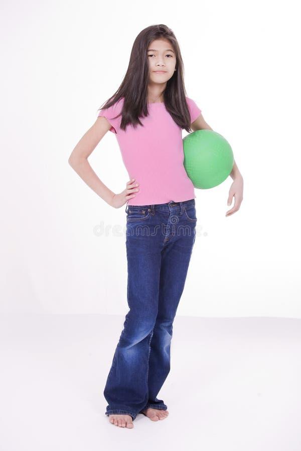 Una ragazza di dieci anni che tiene sfera verde immagine stock