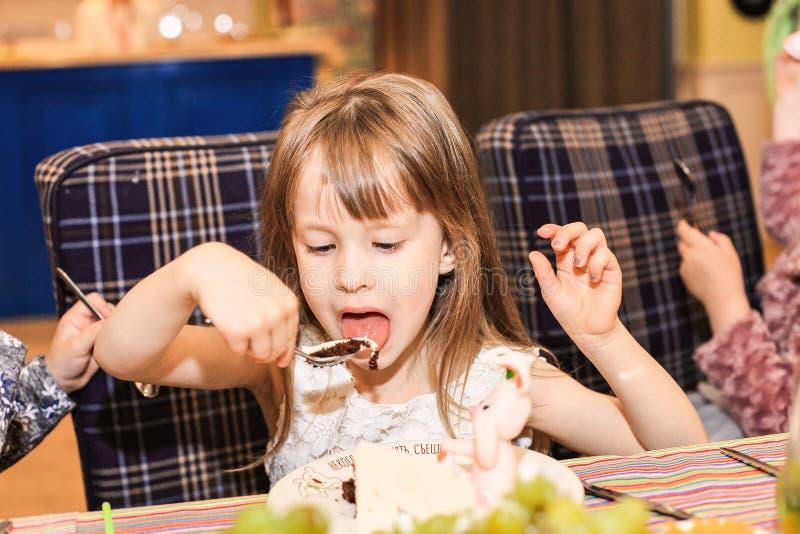 Una ragazza di quattro anni mangia una torta di compleanno fotografia stock libera da diritti
