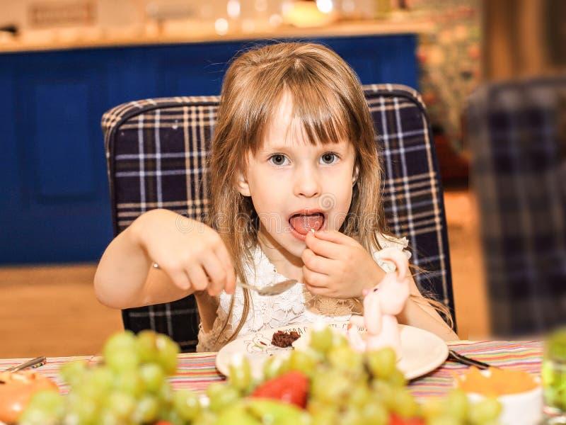Una ragazza di quattro anni mangia una torta di compleanno immagine stock libera da diritti
