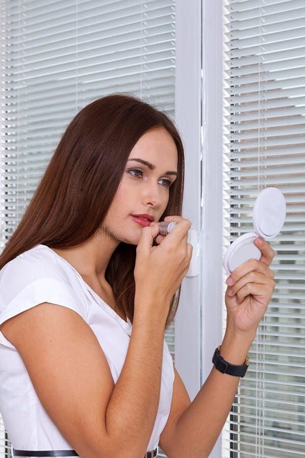 Una ragazza dipinge le labbra con rossetto immagine stock