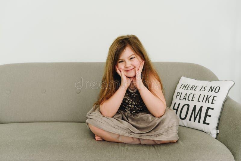 Una ragazza divertente che si siede sul sofà e che sorride ampiamente immagini stock libere da diritti