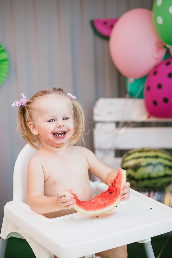 Una ragazza dolce ride mentre si siede in un seggiolone e mangia una fetta di anguria succosa di estate immagine stock