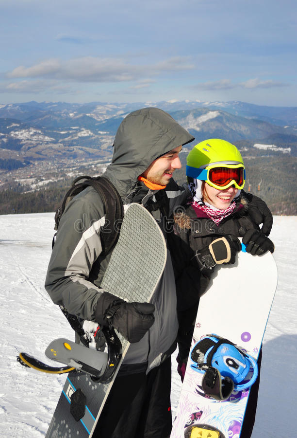Una ragazza e una condizione del ragazzo, sorridenti e tenenti gli snowboads fotografia stock libera da diritti