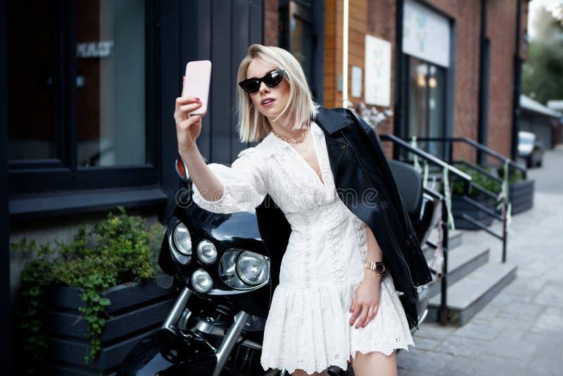 Una ragazza elegante come biker con abiti da moda, vestiti bianchi, giubbotti di cuoio nero, occhiali da sole Blogger di capelli  fotografia stock