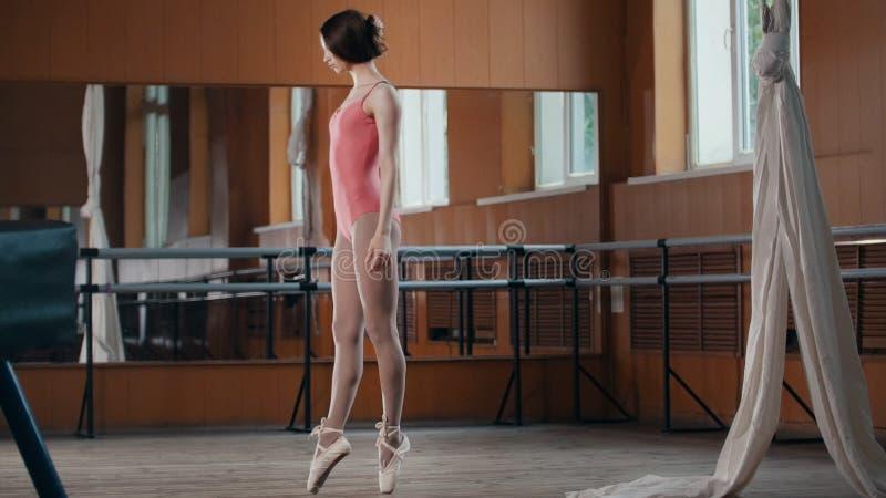 Una ragazza esegue con garbo i trucchi di acrobatica in studio immagini stock