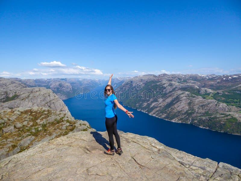 Una ragazza felice che gode della vista del fiordo lei in Norvegia fotografia stock libera da diritti