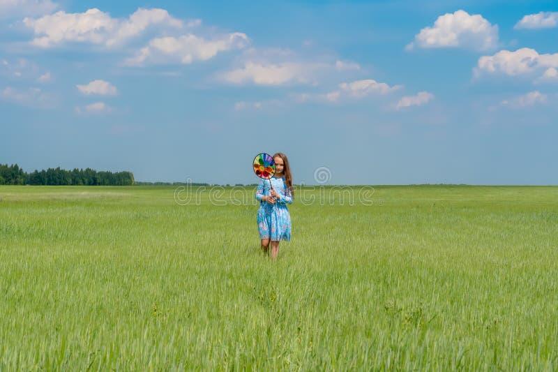 Una ragazza felice con capelli lunghi sta stando sull'erba su un campo verde con un mulino a vento luminoso immagine stock