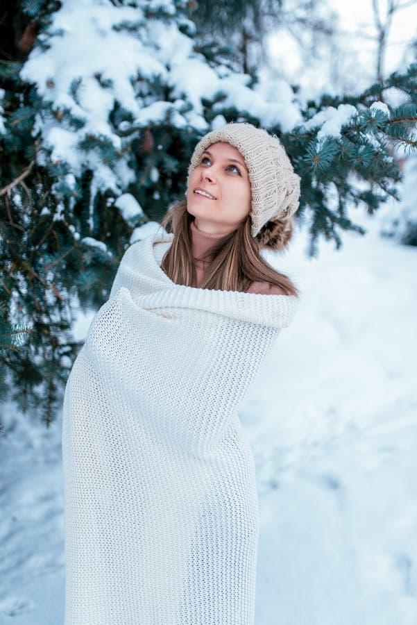 Una ragazza felice nell'inverno nel legno, in maglione bianco e cappello caldo, guarda alla cima Contro lo sfondo di neve fotografia stock libera da diritti