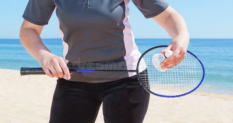 Una ragazza gioca il volano sulla spiaggia. fotografie stock libere da diritti