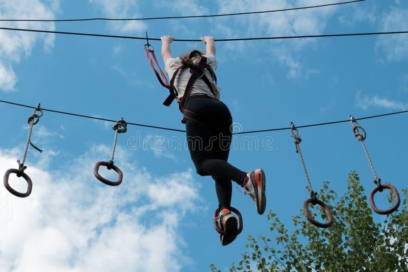 Una ragazza gode di di scalare nell'avventura di corso delle corde Parco rampicante dell'alto cavo copi lo spazio per il vostro t fotografia stock