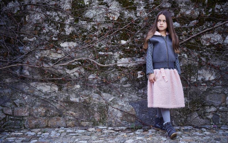 Una ragazza in una gonna e maglia con cappuccio su fondo grigio immagine stock libera da diritti