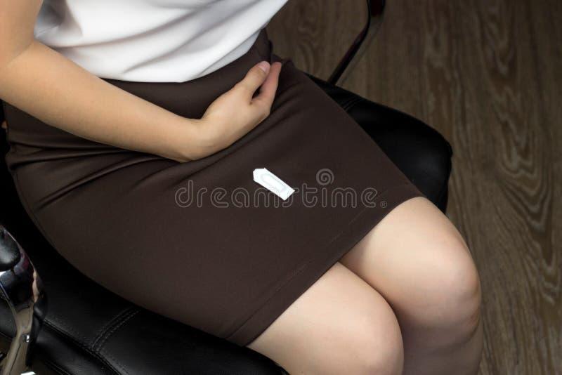 Una ragazza in una gonna si siede in una poltrona sulle sue gambe Ha una supposta, infezione, supposta fotografie stock