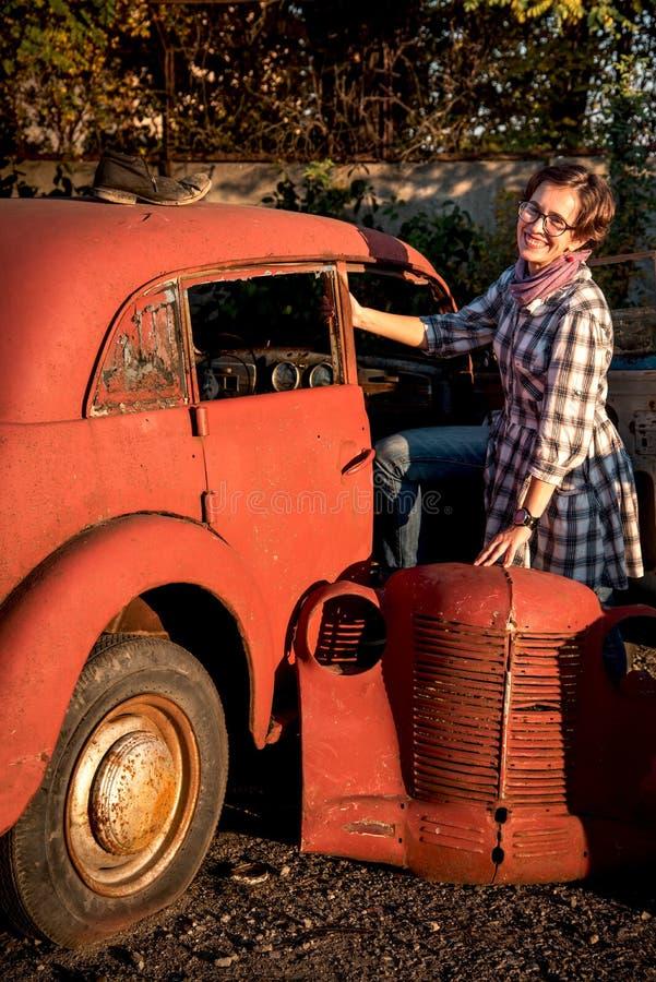 Una ragazza graziosa che posa intorno ad una vecchia retro automobile rossa gettata fotografia stock libera da diritti
