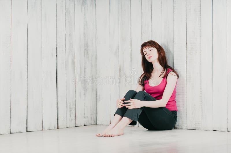 Una ragazza graziosa in una cima rosa, sedentesi sul pavimento nel rilassamento, fotografia stock