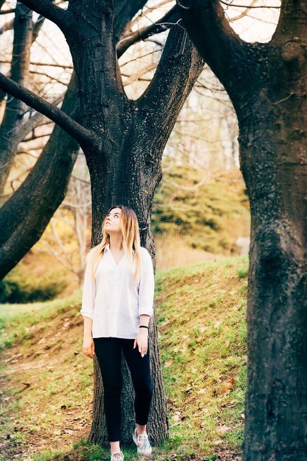 Una ragazza graziosa in un parco con i grandi alberi fotografia stock