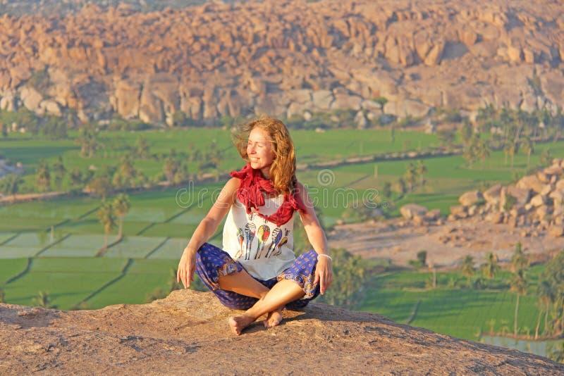 Una ragazza in Hampi, si siede e sorride sulla collina di Anjaneya, Hanuman Temple Rilassi e riposi, solo con la natura Risaie o  fotografia stock
