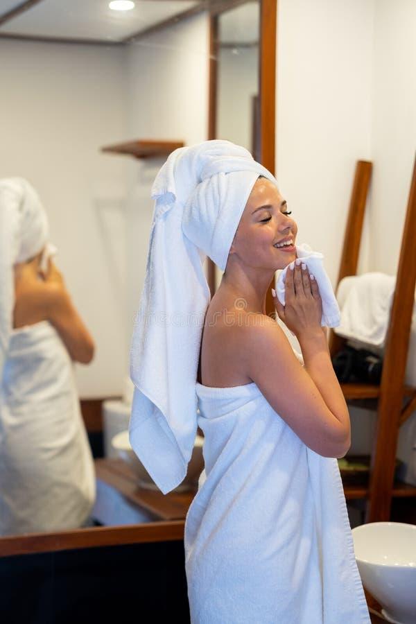 Una ragazza lava il suo fronte La testa ed il corpo della ragazza s sono avvolti in asciugamani bianchi fotografia stock libera da diritti