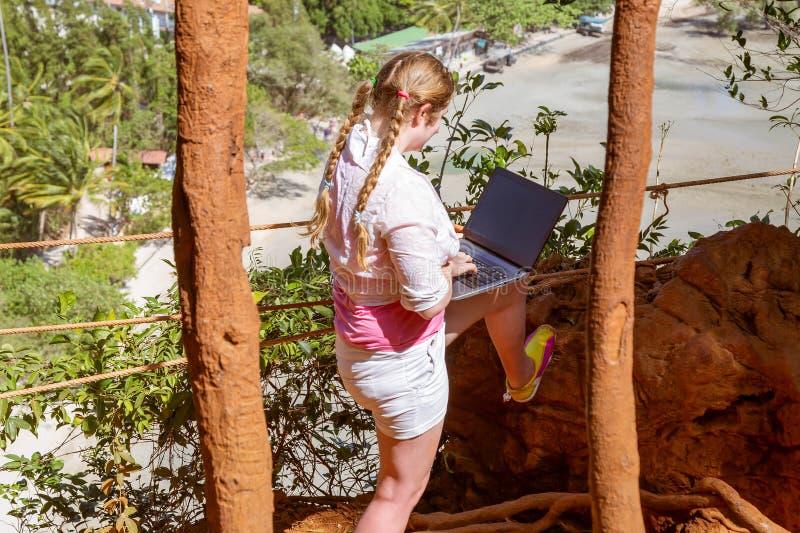 Una ragazza lavora con un computer portatile sulla montagna che trascura la foresta pluviale e la spiaggia Lavoro e viaggio fotografia stock libera da diritti