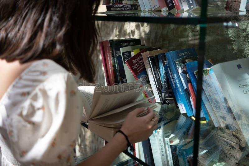 Una ragazza legge un libro aperto, la retrovisione, illuminazione naturale immagini stock libere da diritti