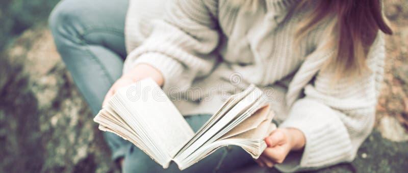 Una ragazza legge un libro sulla vista della natura da sopra fotografia stock