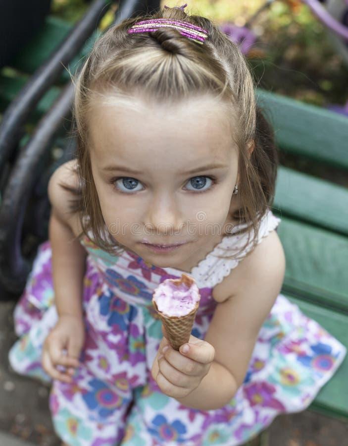 Una ragazza mangia un gelato in parco immagine stock