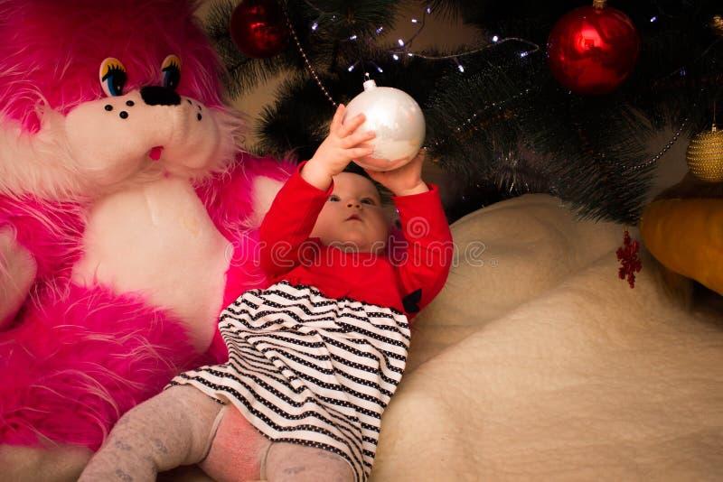 Una ragazza molto piccola si siede sotto un albero di Natale con le decorazioni variopinte Nuovo anno ed albero di Natale fotografie stock libere da diritti