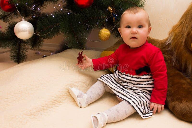 Una ragazza molto piccola si siede sotto un albero di Natale con le decorazioni variopinte Nuovo anno ed albero di Natale immagine stock