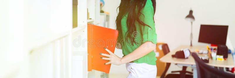 Una ragazza nell'ufficio estrae le cartelle con i documenti fotografie stock