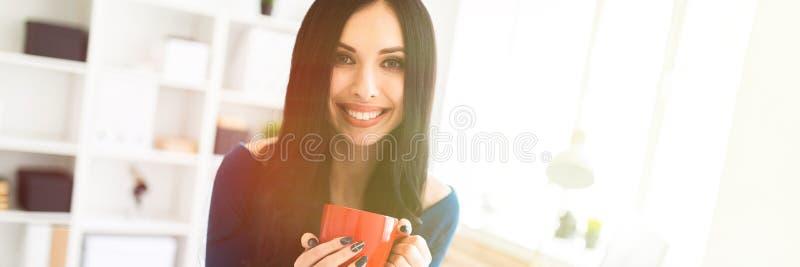 Una ragazza nell'ufficio seduto giù sulla tavola e stava tenendo una tazza rossa in sue mani fotografia stock