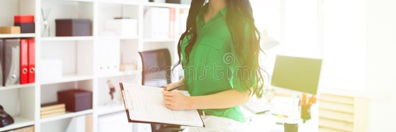Una ragazza nell'ufficio sta tenendo una matita e uno strato per le note immagine stock libera da diritti