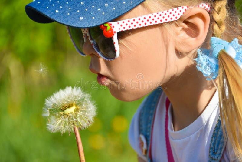 Una ragazza in occhiali da sole nel campo sta soffiando forte ad un dente di leone del fiore, il primo piano, l'estate fotografia stock