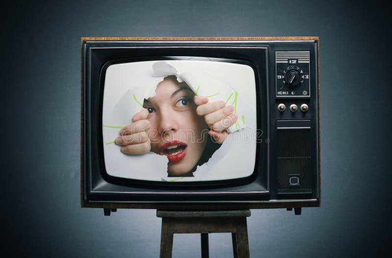 Una ragazza osserva fuori dalla TV. immagine stock