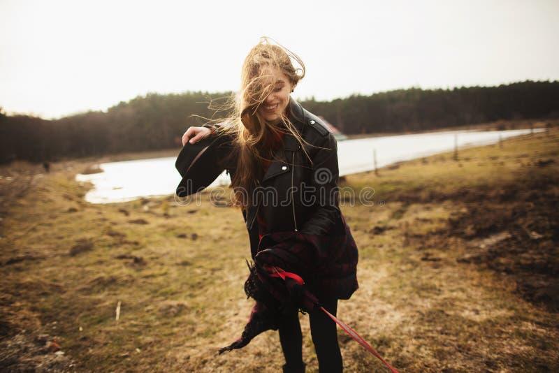 Una ragazza posa sulla riva di un lago, gettante una sciarpa lei fotografia stock
