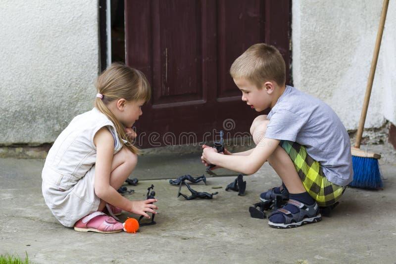 Una ragazza prescolare graziosa bionda di due bambini svegli e ragazzo bello che giocano all'aperto con i giocattoli di plastica  fotografie stock