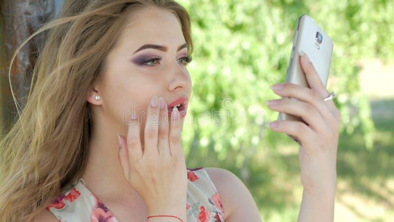 Una ragazza regola il suo trucco con un telefono fotografie stock