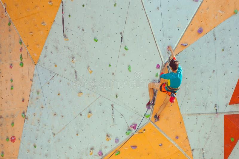 Una ragazza scala una parete rampicante immagine stock