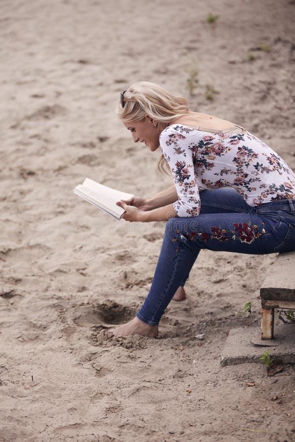 Una ragazza, sedentesi sui punti sulla sabbia della spiaggia, estate, sorridere felice, leggente un libro all'aperto Vista latera fotografie stock