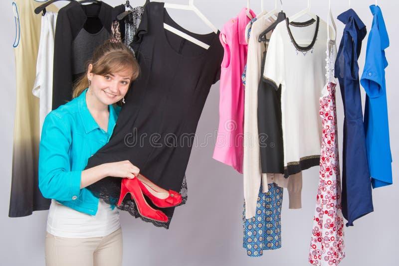 Una ragazza selezionata sul vestito alle scarpe a tacco alto rosse sceglie meditatamente i vestiti in un guardaroba fotografie stock