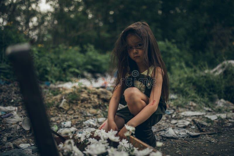 Una ragazza senza tetto sta piantando i fiori in una valigia su una discarica fotografia stock libera da diritti