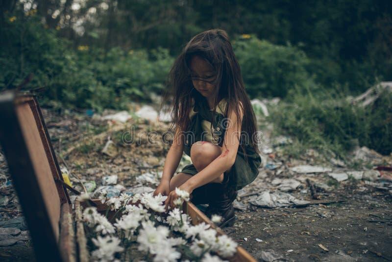 Una ragazza senza tetto sta piantando i fiori in una valigia su una discarica immagini stock
