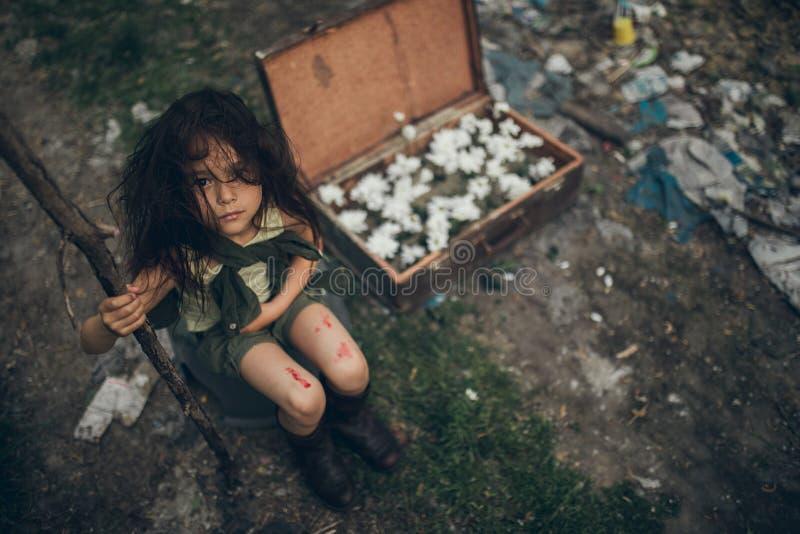Una ragazza senza tetto sta sedendosi su una discarica accanto ad una valigia con i fiori dentro immagini stock