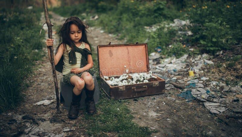 Una ragazza senza tetto sta sedendosi su una discarica accanto ad una valigia con i fiori dentro immagini stock libere da diritti