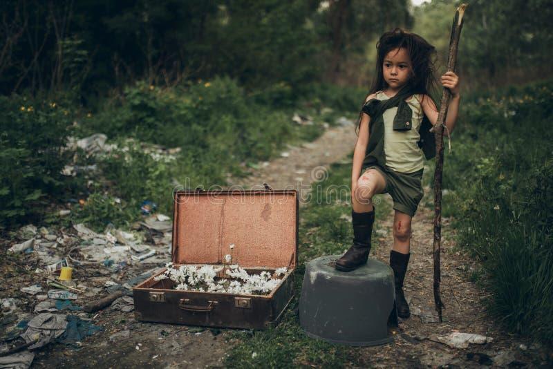 Una ragazza senza tetto sta stando su una discarica accanto ad una valigia con i fiori dentro immagine stock