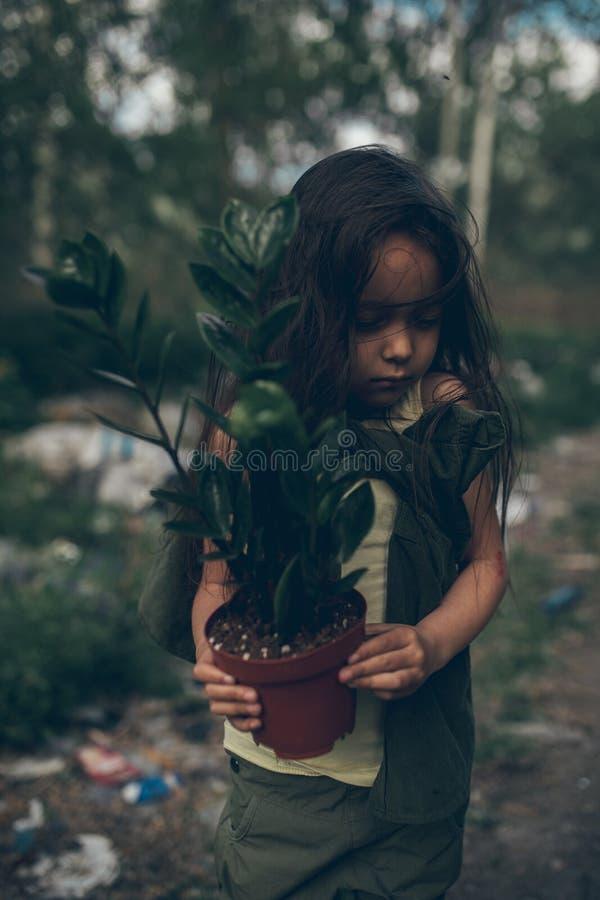 Una ragazza senza tetto sta stando su una discarica con una pianta da appartamento in un vaso immagine stock