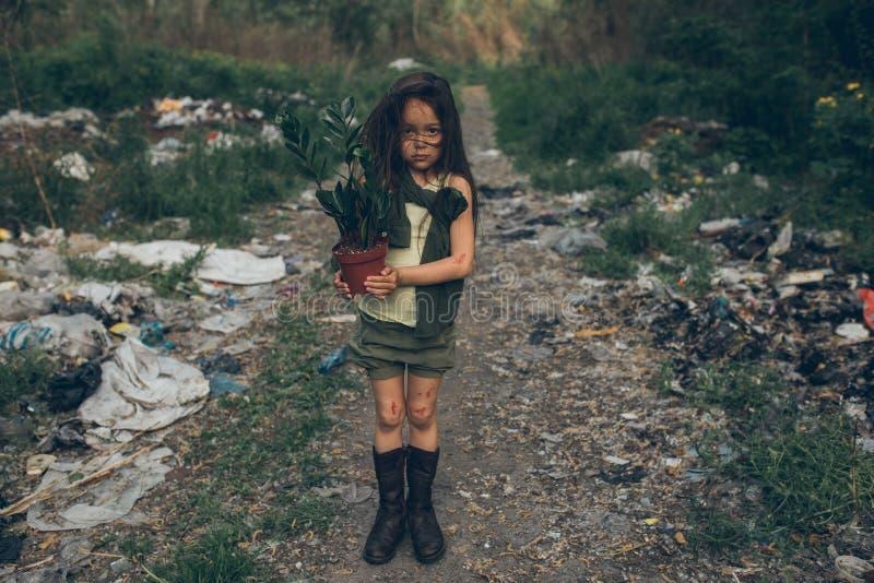 Una ragazza senza tetto sta stando su una discarica con una pianta da appartamento in un vaso fotografia stock libera da diritti