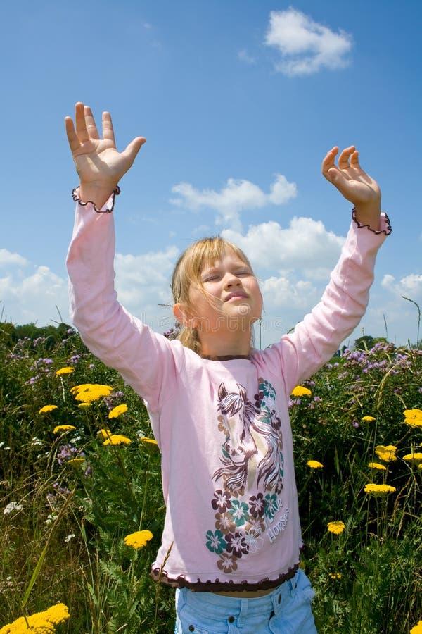 Una ragazza serena con le mani si è alzata nell'elogio. fotografie stock libere da diritti