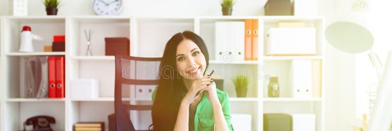 Una ragazza si siede alla tavola dell'ufficio e tiene una matita in sue mani fotografia stock